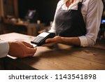 female bartender holding a... | Shutterstock . vector #1143541898
