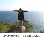 the girl stands on a rock with... | Shutterstock . vector #1143688328