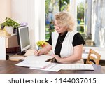 middle aged woman in the office | Shutterstock . vector #1144037015