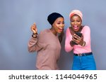 excited girls looking at a... | Shutterstock . vector #1144044965