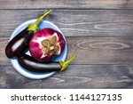 fresh raw purple eggplant on a... | Shutterstock . vector #1144127135