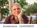mature man smiling and holding...   Shutterstock . vector #1144240925