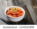 kimchi cabbage in a bowl with... | Shutterstock . vector #1144261898