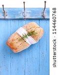 Small photo of Fresh Ciabatta (Italian bread) is hanging headlong on a hook on a blue wooden board, ciabatta bread ready for sale