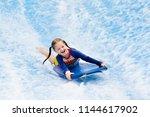 little girl surfing in beach...   Shutterstock . vector #1144617902