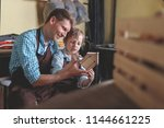 father and son with a wooden... | Shutterstock . vector #1144661225