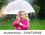 little girl playing in rainy...   Shutterstock . vector #1144710968