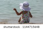 little girl in a big hat sits... | Shutterstock . vector #1144715648