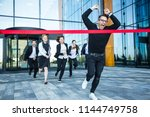 Small photo of Group of happy business people running from office building crossing red ribbon finish line