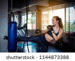 female boxer jump kicking a big ... | Shutterstock . vector #1144873388