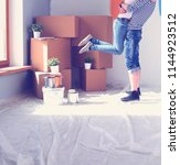 happy young couple moving in... | Shutterstock . vector #1144923512