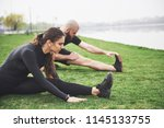 Fitness couple stretching outdoors in park near the water. Young bearded man and woman exercising together in morning.
