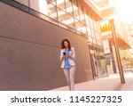 businesswoman looking at her... | Shutterstock . vector #1145227325