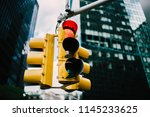 Small photo of Equipment for regulating transport with lambs hanging in downtown in usa,yellow traffic lights controlling cars and supporting safety on crossways in megalopolis with high buildings and construction