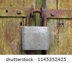 old rusty padlock on the locked ... | Shutterstock . vector #1145352425