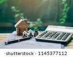house placed on coins. notebook ... | Shutterstock . vector #1145377112