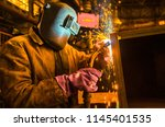 the worker in overalls and a... | Shutterstock . vector #1145401535