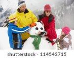 Family Building Snowman On Ski...
