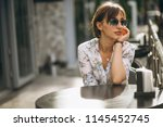 woman sitting outside cafe | Shutterstock . vector #1145452745
