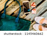 Top view green big casual bag with snake print, round glasses, golden phone and pair of female high-heeled shoes on a wooden background. Modern fashion concept and everyday women