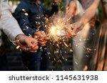 burning sparklers in hands of... | Shutterstock . vector #1145631938