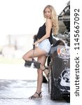 a blonde woman washing a suv car | Shutterstock . vector #1145667092
