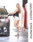 a blonde woman washing a suv car | Shutterstock . vector #1145667095