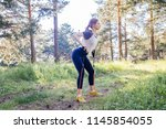 woman doing exercises in a park | Shutterstock . vector #1145854055