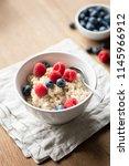 bowl of oatmeal porridge with... | Shutterstock . vector #1145966912