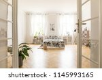 Stock photo sun shinning through windows into a spacious stylish bedroom interior in a villa big bed with 1145993165