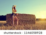 girl leaning on a straw bale in ... | Shutterstock . vector #1146058928