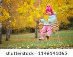 little girl on swings in autumn ... | Shutterstock . vector #1146141065