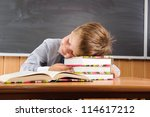 Sleeping  elementary aged boy sitting at the desk with books - stock photo