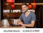 handsome man sitting in cafe ... | Shutterstock . vector #1146211985