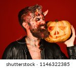 man wearing scary makeup holds... | Shutterstock . vector #1146322385