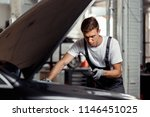 a young car mechanic is... | Shutterstock . vector #1146451025