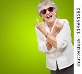 Stock photo senior woman wearing sunglasses doing funky action isolated on green background 114691282