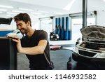 smiling mechanic checking a car ... | Shutterstock . vector #1146932582