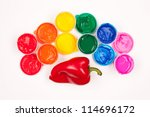 motley paints on the white background. paints arranged as rainbow with red sweet pepper (paprika). studio shot - stock photo
