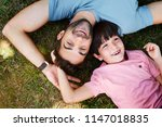 son and dad lying on grass ... | Shutterstock . vector #1147018835