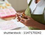 hands of woman wrapping small... | Shutterstock . vector #1147170242