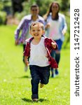 little boy running and parents... | Shutterstock . vector #1147212428