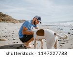 man playing with dog at the... | Shutterstock . vector #1147227788