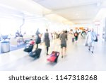 Small photo of Blurry background flight attendants walking through airport hallway with suitcase. Motion blurry people walk away with luggage at American terminal. Travel and transportation concept