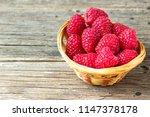 raspberries  in a basket on a... | Shutterstock . vector #1147378178