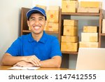 courier man sitting and smiling ... | Shutterstock . vector #1147412555
