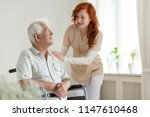 smiling caregiver helping... | Shutterstock . vector #1147610468