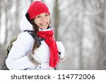Woman winter hiking. Beautiful young Asian woman enjoying the falling snow dressed in a cheerful red winter scarf and cap and with a satchel on her back with copyspace. - stock photo