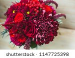 Beautiful bouquet of flowers on a wooden background. Chrysanthemums, asters, roses and berries. Red and burgundy flowers. - stock photo