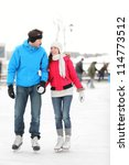 Romantic young couple in warm winter clothing holding hands and smiling at each other while ice skating. - stock photo